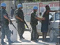 Soldados brasileños de la ONU registran a un hombre en Puerto Príncipe