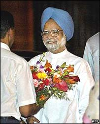 Manmohan Singh receives flowers as he arrives at the prime minister's residence