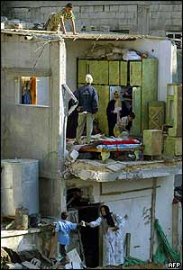 A Palestinian family examine the remains of their home
