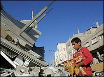 A boy carries supplies of pasta through the wreckage of Rafah refugee camp