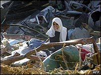 A woman sits amid the rubble of her house in Rafah refugee camp