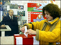 Belarusian votes early in front of Lukashenko poster