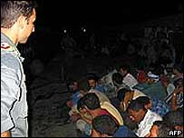 Italian policeman looks at illegal migrants on Lampedusa