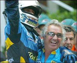 Trulli jumps into the arms of Renault team boss Flavio Briatore after securing his maiden F1 victory