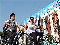 Two schoolboys cycle along the National Assembly Building in Hanoi, Tuesday Sept. 5, 2004