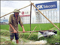 A farmer uses a traditional way to water his rice field next to huge advertising posters for local and foreign companies in the suburbs of Hanoi, 23 July 2002.