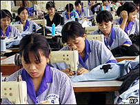 Vietnamese workers use sewing machines at a state run garment factory, 2001