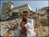 Zaki Ajrami and his son Ahmed sit on the rubble of their destroyed house in Jabaliya refugee camp