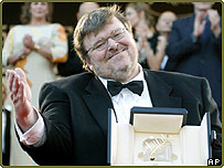 Michael Moore holds his Palme d'Or prize at Cannes