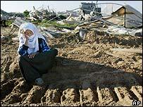 Palestinian woman sits in Israeli bulldozer tracks in devastated Tel Sultan farmland