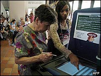 An election worker shows a lady how to vote in Miami
