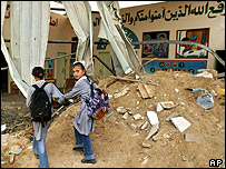 Young Palestinian girls walk past destroyed school in Beit Lahiya, northern Gaza Strip
