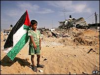 Palestinian boy holds flag by demolished homes in Jabaliya refugee camp