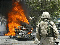 US troops in Iraq guard the burning wreckage of a car destroyed in a rocket attack