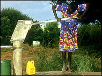 A woman pumping water from a well