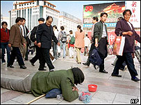 A beggar lies outside the Beijing Railway Station (archive picture)