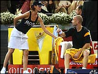 A model hands Andre Agassi a towel