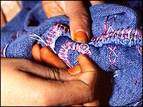 Woman embroiders a pair of Ermanno Scervino designer jeans