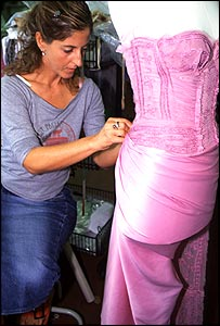 ES employee puts the finishing touches on a pink stitched bodice