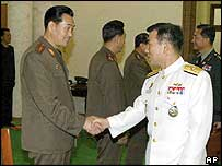 South Korea's delegation leader Rear Adm Park Jung-hwa, right, shakes hands with unidentified North Korean