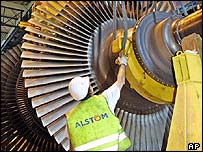 An Alstom worker adjusts a massive turbine
