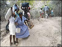 People carry their belongings across treeless slopes near St Marc, Haiti