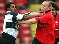 Wales full-back Gareth Thomas uses his strength to make a break