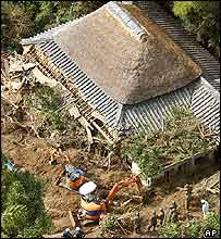 Rescuers and Self-Defence Force soldiers, in green, search through a house destroyed by landslides on Awaji island, western Japan, Thursday, Oct. 21, 2004