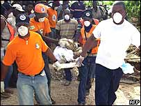 Rescue workers carry the body of a flood victim in Jimani, Dominican Republic