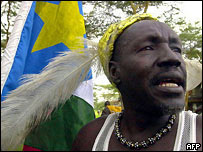 An unidentified Sudanese man sporting a traditional hat sings while holding a SPLA flag in Naivasha, Kenya