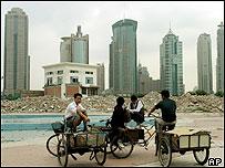 Chinos en biciletas frente a edificios.