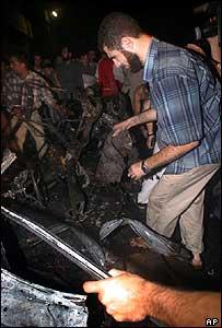 Man looks at wreck of Adnan al-Ghoul's car