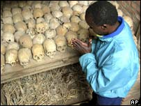 A survivor of the 1994 genocide in Rwanda prays over the bones of genocide victims at a mass grave in Nyamata