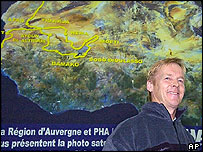 Race car driver and MEP Ari Vatanen stands in front of a map of the Paris to Dakar rally