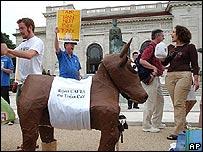 Manifestantes con un caballo de juguete.