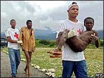 Members of the Red Cross help two victims of the flood in the Dominican town of Jimani