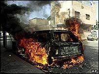 سيارة أشعل محتجون النار فيها في كراتشي بعد مقتل نظام الدين