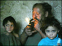 A Roma man lights up a cigarette in his hut in eastern Slovakia
