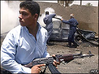 Iraqi security officer standing in front of a burning car in Baghdad