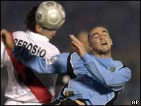 El uruguayo Walter Pandiani (der.) disputa el balón con César Rebosi del Perú.