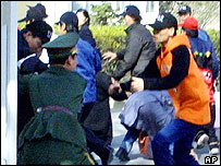 A Chinese military police guard, left, struggles to hold back a group of North Korean asylum-seekers at the Spanish Embassy in Beijing Thursday March 14, 2002