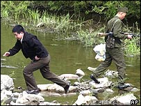 A Chinese tourists runs back after giving a bag of food to an armed North Korean border guard in the middle of a stream which marks the China-North Korea border, Sunday April 25, 2004