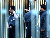 Chinese policemen trying to figure out what happened after North Korean refugees managed to enter a German embassy school in Beijing, China, Tuesday, June 1, 2004