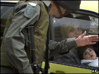 An Israeli border policeman checks a car