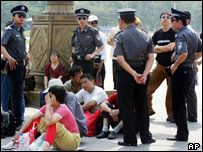 Chinese police surround a group of people on Tiananmen Square on 3 June 2004