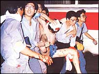 Students carry bullet-wounded man to hospital, 4 June 1989 (photo 64memo.com)