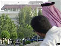 Saudis hide behind a wall as they watch the recent shootout between security forces and gunmen in Khobar