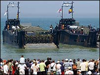 Veterans, tourists and local people watch as a small flotilla of landing Crafts of 4 Assault Squadron Royal Marines land on the beach at Asnelles