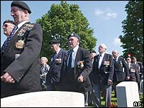 Veterans march through the Commonwealth War Graves Cemetery at Bayeux, France