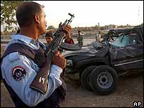 Iraqi police secure the area around a bullet-riddled vehicle, Baghdad, May 2004